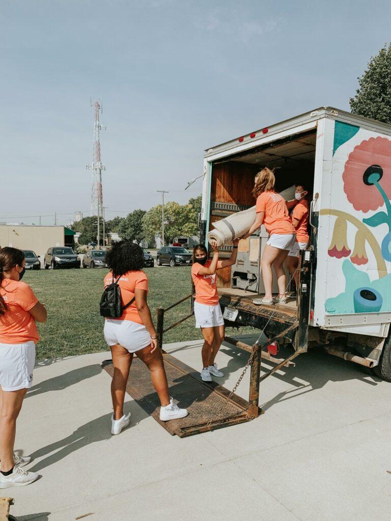 Midland University Women's Lacrosse Volunteers Unloading a Truck